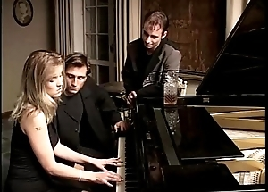 Beauteous whore playing piano together with two cocks